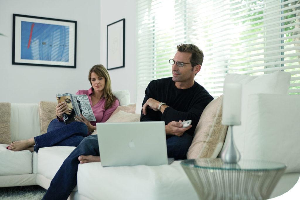Paar entspannt im Wohnzimmer bei halb offenen Innenjalousien