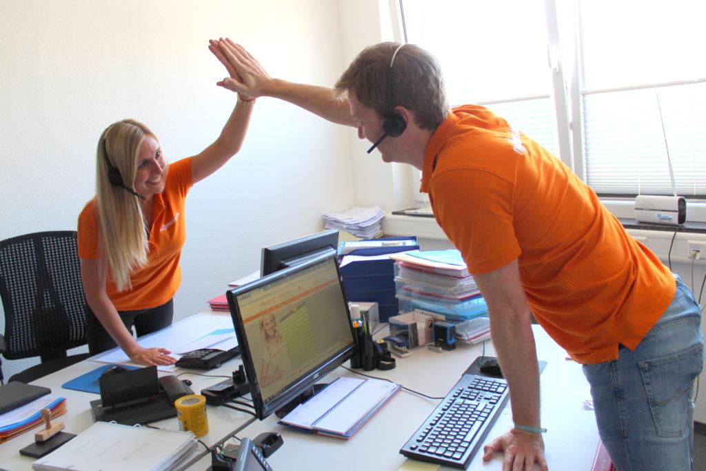 Zwei Mitarbeiter von Rollomeister geben sich ein High Five für die erfolgreiche Zusammenarbeit