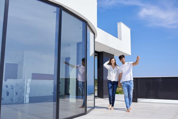 Junges Paar läuft zur Besichtigung des Hauses an der Glasfassade entlang
