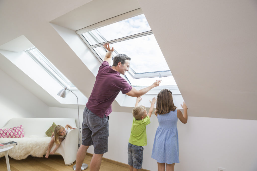 Vater montiert mit seinen Kinder das Insektenschutz Rollo an ein Dachfenster