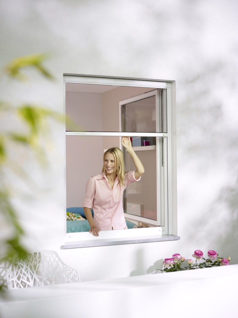 Frau öffnet am Morgen ihr Inesktenschutz Rollo