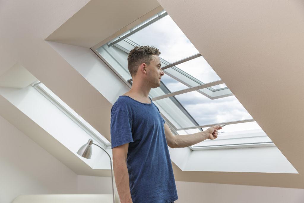 Mann öffnet seinen Insektenschutz Schieberahmen an einem Dachfenster