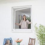Frau montiert Spannrahmen an ihrem Fenster