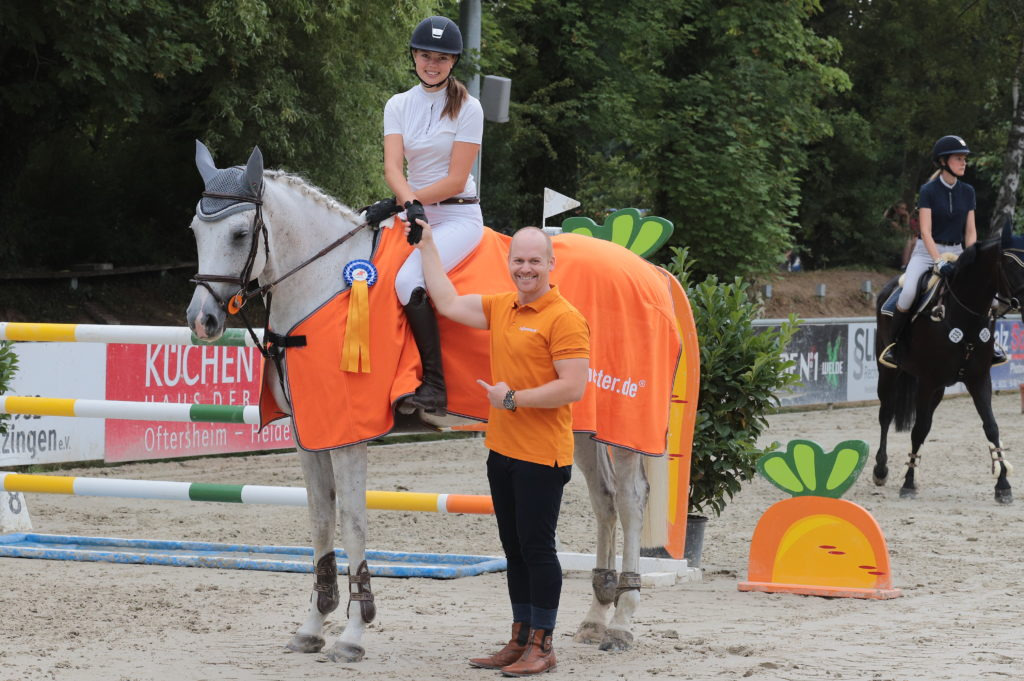 Hier gratuliert der Geschäftsführer von Rollomeistereiner erfolgreichen Reiterin zu ihrer Erstplatzierung und belohnt sie mit einer orangenen Pferdedecke mit dem Rollomeister Werbelogo auf dem Springplatz