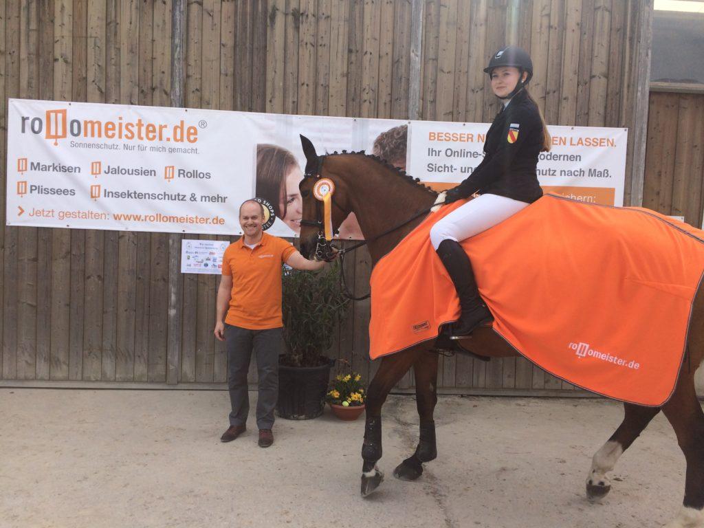 Ein Bild mit dem Geschäftsführer von Rollomeister und einer sehr gut platzierten Reiterin, welche eine ROllomeister Pferdedecke auf dem Hof erhalten hat
