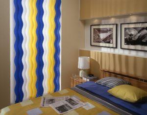 Gelb, weiß, blaue Waveline Lamellen im stylischen Schlafzimmer