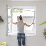 Frau montiert Spannrahmen an ihr Fenster