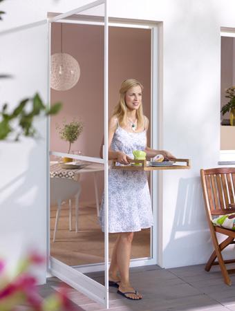 Frau betritt die Terrasse durch geöffnete Drehtür
